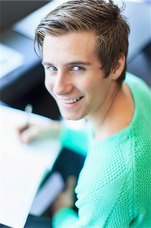 Portrait of a happy young man writing notes in classroom Stock Photo - Premium Royalty-Free, Code: 698-06374974