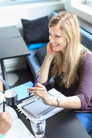 Happy young woman sitting with books at table in university canteen Stock Photo - Premium Royalty-Free, Code: 698-06374978