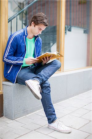 Young male student studying while sitting on stone bench Stock Photo - Premium Royalty-Free, Code: 698-06375004