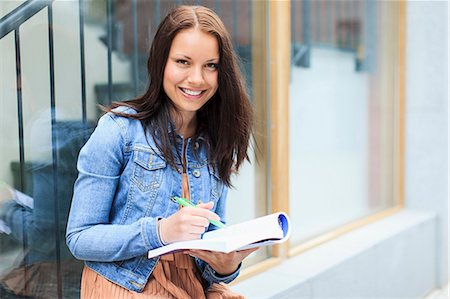 Portrait of a happy young female student with book and pen Stock Photo - Premium Royalty-Free, Code: 698-06375008