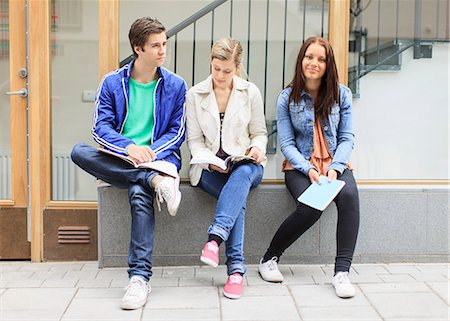 Young friends with books sitting on stone bench in university campus Stock Photo - Premium Royalty-Free, Code: 698-06375003