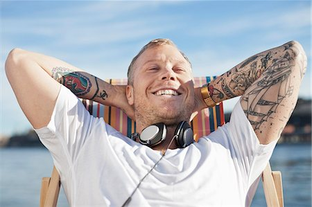 Happy man with tattooed hands relaxing on deck chair at beach Stock Photo - Premium Royalty-Free, Code: 698-06375052