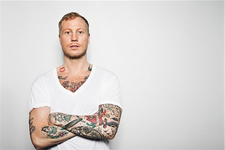 Portrait of a tattooed man with arms crossed standing against grey background Stock Photo - Premium Royalty-Free, Code: 698-06375067