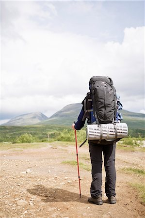 Rear view of a woman with backpack holding hiking pole Stock Photo - Premium Royalty-Free, Code: 698-06375106
