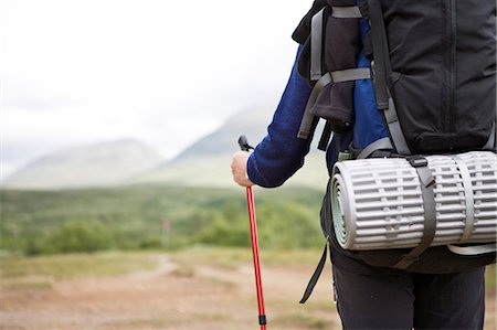Midsection of a woman with backpack holding hiking pole Stock Photo - Premium Royalty-Free, Code: 698-06375107