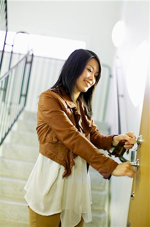 Mid adult woman unlocking door with keys Stock Photo - Premium Royalty-Free, Code: 698-06375134
