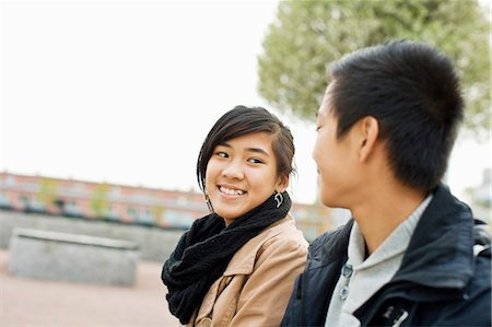 Happy teenage friends looking at each other and smiling Stock Photo - Premium Royalty-Free, Code: 698-06375145
