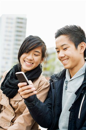 Cheerful teenage friends using smart phone together Stock Photo - Premium Royalty-Free, Code: 698-06375147