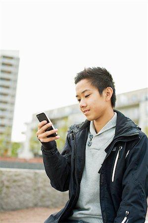 Teenage boy using smart phone Stock Photo - Premium Royalty-Free, Code: 698-06375148