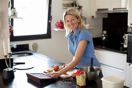 recipe - Mid adult woman using recipe on digital table and making meal in kitchen Stock Photo - Premium Royalty-Free, Code: 698-06375171