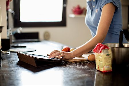 recipe - Mid section of woman looking for recipes in digital tablet at kitchen Stock Photo - Premium Royalty-Free, Code: 698-06375172