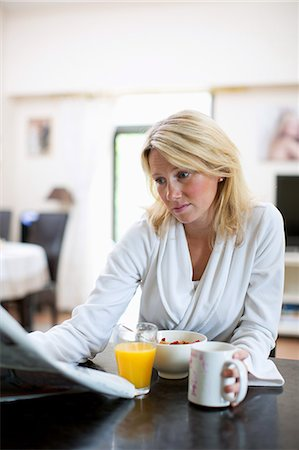 Mid adult woman in bathrobe reading newspaper while having breakfast Stock Photo - Premium Royalty-Free, Code: 698-06375180