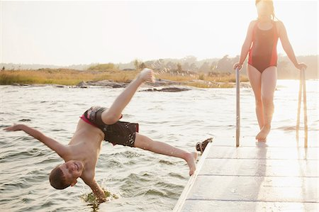 Little boy jumping in water with sister standing on pier Stock Photo - Premium Royalty-Free, Code: 698-06375195