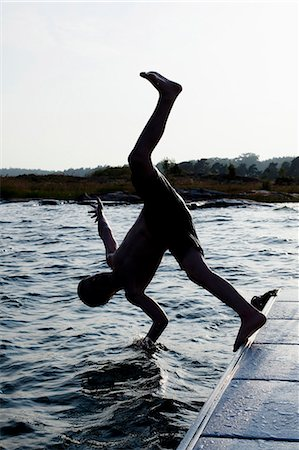 Silhouette of a little boy diving into water Stock Photo - Premium Royalty-Free, Code: 698-06375196
