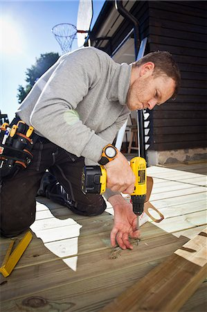 Manual worker drilling nail on floorboard Stock Photo - Premium Royalty-Free, Code: 698-06375232