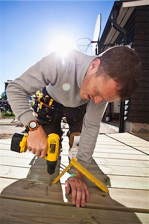 drilling - Manual worker drilling nail on floorboard against sunbeam Stock Photo - Premium Royalty-Free, Code: 698-06375233