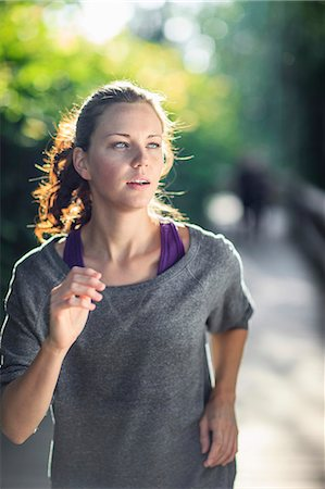 Young woman looking away as she jogs Stock Photo - Premium Royalty-Free, Code: 698-06375324