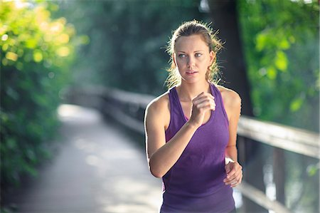 Healthy female jogging down track Stock Photo - Premium Royalty-Free, Code: 698-06375325