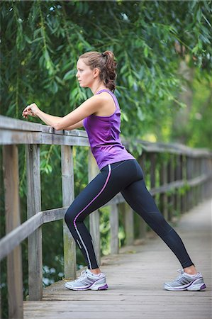 Side view of young woman stretching on fence Stock Photo - Premium Royalty-Free, Code: 698-06375334