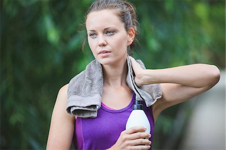 Tired young woman holding water bottle with towel around neck Stock Photo - Premium Royalty-Free, Code: 698-06375338