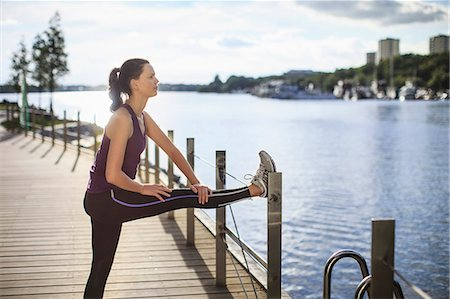 Side view of young woman stretching leg on fence Stock Photo - Premium Royalty-Free, Code: 698-06375330