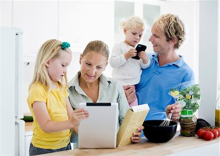 Family using digital tablet for cake making recipe in kitchen Stock Photo - Premium Royalty-Free, Code: 698-06375349