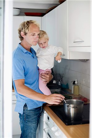 stove - Man preparing food while holding daughter in kitchen Stock Photo - Premium Royalty-Free, Code: 698-06375354