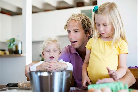 Amazed man looking at little daughter breaking egg in kitchen Stock Photo - Premium Royalty-Free, Code: 698-06375364
