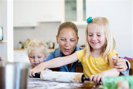 Happy woman looking at little daughter rolling dough on table in kitchen Stock Photo - Premium Royalty-Free, Code: 698-06375365