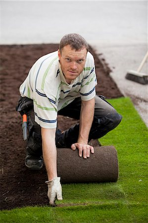 Portrait of a mid adult man rolling new grass turf in lawn Stock Photo - Premium Royalty-Free, Code: 698-06375476