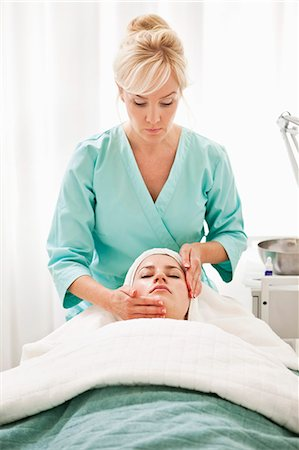 facial - Young woman getting a face massage from blond beautician in health spa Stock Photo - Premium Royalty-Free, Code: 698-06375496