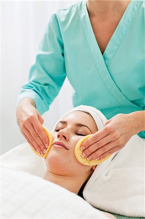 facial - Midsection of a female beautician rubbing sponge on young woman's face Stock Photo - Premium Royalty-Free, Code: 698-06375491