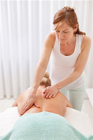 Mature masseur giving a back massage to female customer at health spa Stock Photo - Premium Royalty-Free, Code: 698-06375535