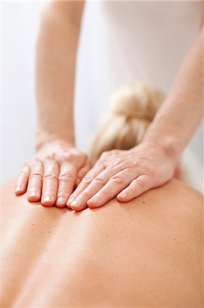 Rear view of a mid adult woman receiving back massage from mature therapist at health spa Stock Photo - Premium Royalty-Free, Code: 698-06375537