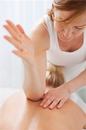 Mature therapist massaging mid adult woman's back with elbow Stock Photo - Premium Royalty-Free, Code: 698-06375538