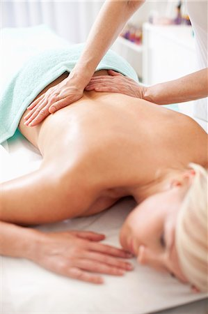 Mid adult woman receiving back massage from masseur at health spa Stock Photo - Premium Royalty-Free, Code: 698-06375530