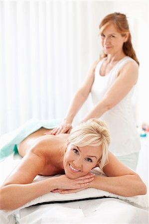 Portrait of a happy mid adult woman lying naked while receiving back massage from masseur Stock Photo - Premium Royalty-Free, Code: 698-06375532