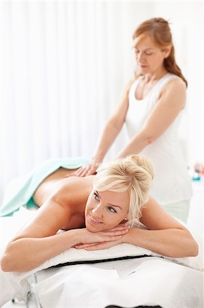 Happy mid adult woman looking away while lying on massage table with masseur in background Stock Photo - Premium Royalty-Free, Code: 698-06375533