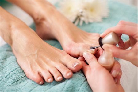 Close-up of a female feet receiving a beauty treatment for nails in spa Stock Photo - Premium Royalty-Free, Code: 698-06375542