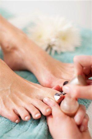 Close-up of a beautician applying nail polish on female customer's toenail in beauty spa Stock Photo - Premium Royalty-Free, Code: 698-06375543