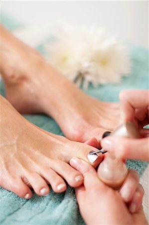 Close-up of a beautician applying nail polish on female customer's toenail in beauty spa Stock Photo - Premium Royalty-Free, Code: 698-06375543