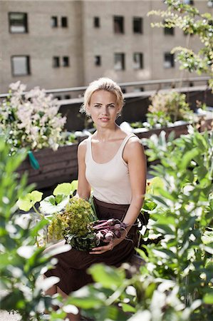 Portrait of young woman sitting at urban garden Stock Photo - Premium Royalty-Free, Code: 698-06444208