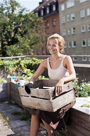 Happy young woman with wooden crate sitting at urban garden Stock Photo - Premium Royalty-Free, Code: 698-06444203