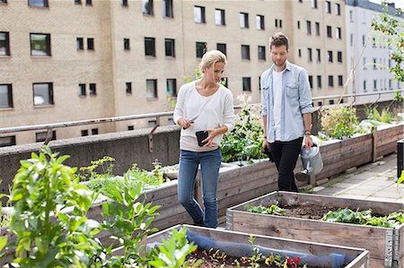 Young Caucasian couple examining potted plants at urban garden Stock Photo - Premium Royalty-Free, Code: 698-06444224