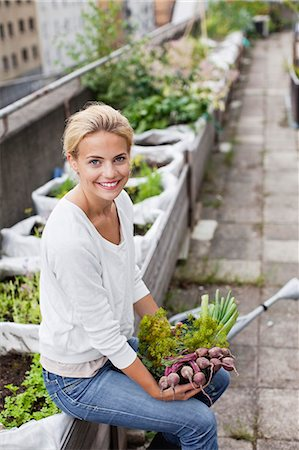 Portrait of happy young woman with freshly harvested vegetables at urban garden Stock Photo - Premium Royalty-Free, Code: 698-06444234
