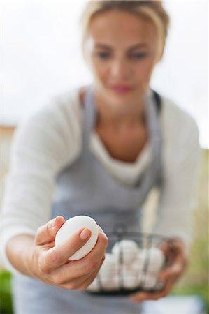 selecting - Young woman picking eggs at urban garden Stock Photo - Premium Royalty-Free, Code: 698-06444239