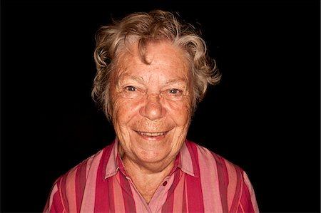 Portrait of happy senior woman against black background Stock Photo - Premium Royalty-Free, Code: 698-06444281