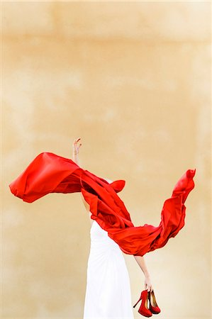 Woman throwing red material while holding high heels against beige background Stock Photo - Premium Royalty-Free, Code: 698-06444382