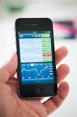 Man's hand showing business graph on smart phone Stock Photo - Premium Royalty-Free, Code: 698-06444391