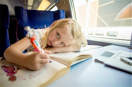 Portrait of girl drawing pictures while sitting on train's seat Stock Photo - Premium Royalty-Free, Code: 698-06444446